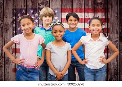 Cute pupils smiling at camera in classroom against composite image of usa national flag