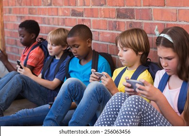 Cute pupils using mobile phone at the elementary school