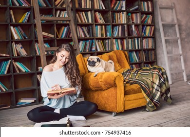 Cute reading lovers family. Beautiful woman sitting on the floor in the library and her lovely dog pug looking to the book too. Happy home weekend moment