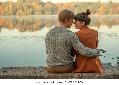 Cute red haired couple of man and woman in casual outfit on a date. They walking in autumn park near river and smiling, hugging and having fun. Warm sunny weather. Space for text