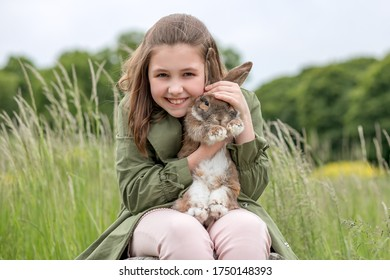 Cute red haired domestic rabbit. The girl holds a fluffy animal in her arms. Love and devotion to a close friend. Pet care concept