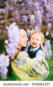 Cute red-haired baby boy laughing in his mother's arms under a wysteria tree