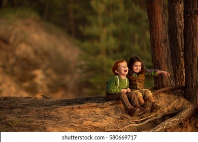 Cute red-haired boy and beautiful little girl are sitting on the tree roots in the forest and laughing. Image with selective focus and toning.