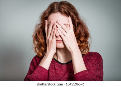 cute red-haired girl closes eyes with hands, isolated on gray background