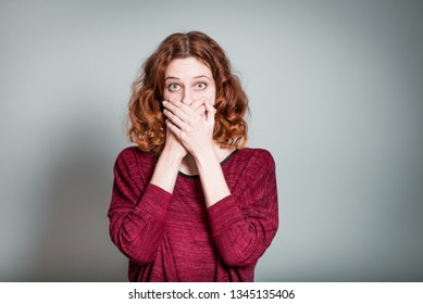 cute red-haired girl frightened and covers mouth with hands, isolated on gray background