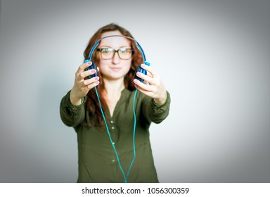 cute red-haired girl gives a listen to music on headphones, wears glasses, isolated on gray background