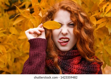 cute red-haired girl on the background of an autumn tree with a leaf in her hand smiles and grimaces.