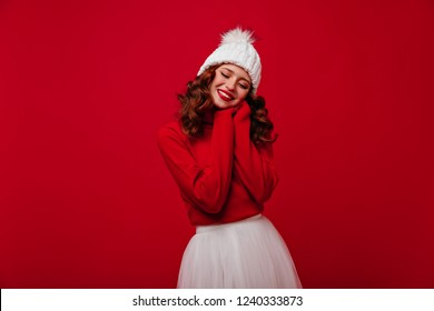 Cute red-haired girl in stylish winter hat expressing happiness in christmas. Attractive young woman in sweater and skirt enjoying new year photoshoot.