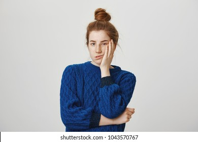 Cute redhead annoyed woman standing in winter sweater, holding palm on cheek and leaning face on it, being bored and tired of uninteresting talks, feeling indifferent to what happening over gray wall