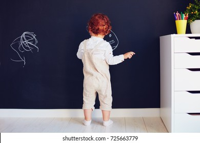 cute redhead baby boy drawing on the chalk wall at home