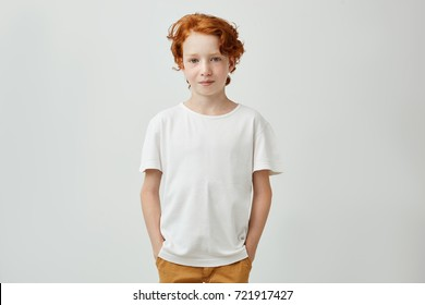 Cute redhead boy with good-looking hairstyle in white t-shirt holding holding hands in pockets, gently smiling and looking in camera.