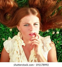 Cute redhead female lying down on fresh green grass