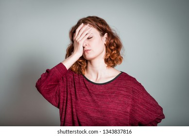 cute redhead girl forgot something important isolated on gray background
