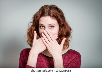 cute redhead girl hides face with hands, isolated on gray background
