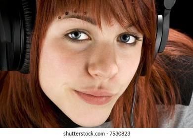 Cute redhead girl looking seductively at camera, smiling, and listening to music on headphones. Studio shot.