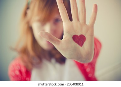 Cute redhead girl showing heart painted on her palm - retro/vintage color