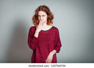 cute redhead girl shows nausea, isolated on gray background