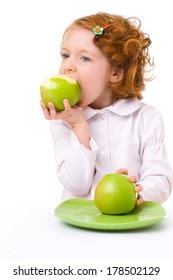 cute redhead little girl with green apples, isolated over white
