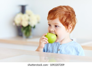 cute redhead toddler baby biting tasty green apple