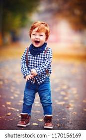 cute redhead toddler baby boy walking among fallen leaves on autumn street