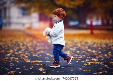 cute redhead toddler baby boy walking in autumn park with plush toy in hands