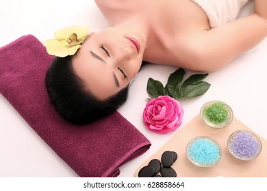 Cute relaxed young woman laying in spa salon with closed eyes