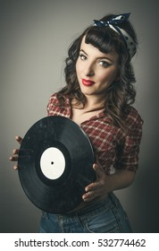 Cute retro pin up girl with a vintage hairstyle in ringlets and bobs and bandanna in her hair standing holding a vinyl record in her hands smiling at the camera in a beauty portrait