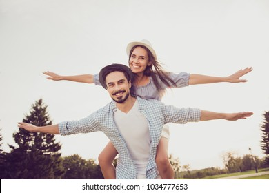 Cute romantic bearded brunet in checkered shirt, dreamy lady rides him on rear. Leisure, chill happiness, lawn stroll, relax, romance lifestyle, well dressed in blue, partners posing in headwear