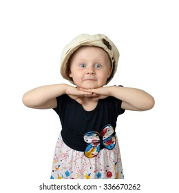 Cute round faced little girl with amazed facial expression and hands under chin posing in too big cap isolated on white background in square