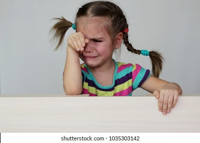 Cute sad 5 years old girl with funny pigtails crying over white background, space for copy, advertising and announcement concept, studio shot