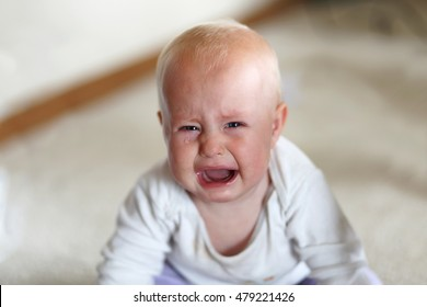 A cute, but sad 6 month old baby girl is crying as she looks at the camera in her home.