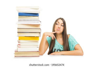 Cute sad Caucasian teenage girl with stack of books thinking sitting at the table looking sideways. Education concept. Isolated on white background.