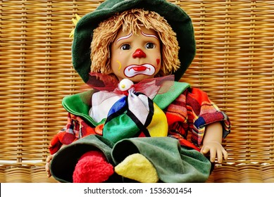 Cute sad joker baby doll, Beauty of colorful joker doll sitting in the basket.