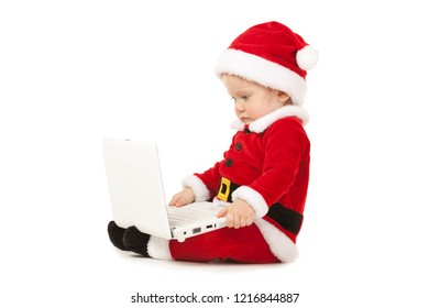 Cute santa baby on the white background. Small model in santa hat at studio holding white laptop. Christmas, xmas, winter concept. Santa girl looking at white laptop