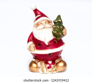 Cute Santa Claus doll with a Christmas tree in his hand. Adorable Santa Claus decorative toy, insulator on a white background. Christmas and New Year symbols.