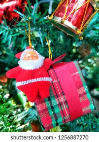 Cute Santa Claus doll with gift box hanging on Christmas tree on blurred green background and bokeh for illustration Christmas festival.