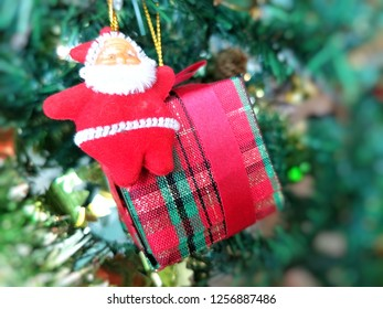 Cute Santa Claus doll with gift box hanging on Christmas tree on blurred green background for illustration Christmas festival.