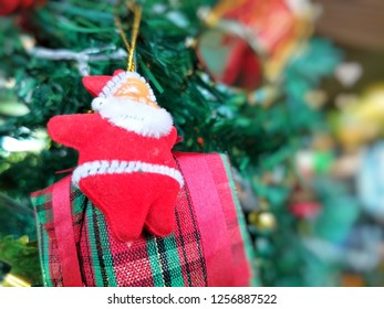Cute Santa Claus doll with gift box hanging on Christmas tree on blurred green background and heart shape bokeh for illustration Christmas festival.
