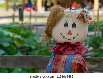 Cute scarecrow doll with a plaid top and ruffle collar on a bench with out of focus greenery in the background
