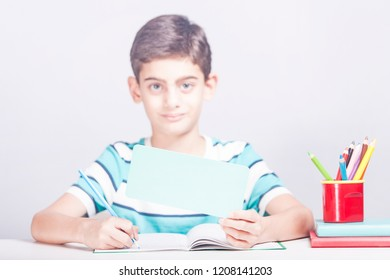 Cute school boy holding a blank advertising banner with copy space. (Selective focus image)