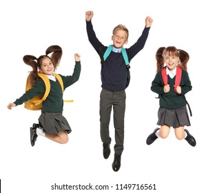 Cute school children in uniform with backpacks jumping on white background