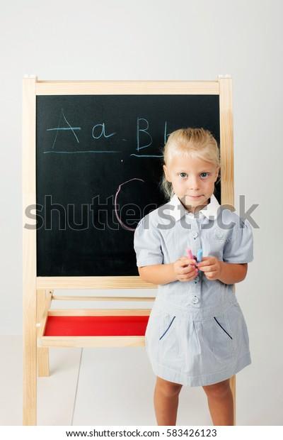 cute school girl drawing on blackboard