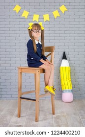 Cute school girl posing in studio shoot in school uniform dress and jacket on background of letters or grey brick wall. Teen holding books and huge pencils. Schoolgirl wearing yellow stylish shoes.