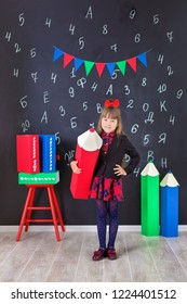 Cute school girl posing in studio shoot in school uniform dress and jacket on background of letters or grey brick wall. Teen holding books and huge pencils.On books written names of school subjects.