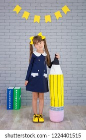 Cute school girl posing in studio shoot in school uniform dress and jacket on background of letters or grey brick wall. Teen holding books .On books written on russian names of school subjects