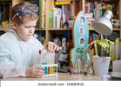 Cute school kid boy sitting at the table making science experiments at home. Learning activities with children at home. Doing water tests. Future profession - scientist.