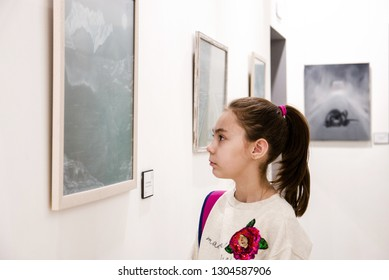 Cute school-age girl at the exhibition of paintings by young artist Katie Melkadze in Moscow on February 3, 2019