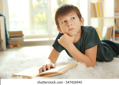 Cute schoolboy with book on carpet on floor