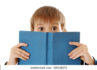 Cute schoolboy closing his face with book on white background, closeup