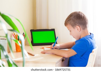 Cute schoolboy drawing picture, tablet with green screen stay on desk. Education and distance learning concept.
